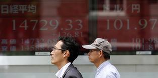 Люди проходят мимо брокерской конторы в Токио 27 мая 2014 года. Азиатские фондовые рынки завершили торги четверга разнонаправлено под влиянием итогов совещания ФРС и местных факторов. REUTERS/Toru Hanai
