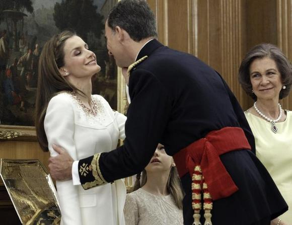 Spain's new King Felipe VI (C), wearing the Sash of Captain-General, kisses his wife Queen Letizia as his mother Queen Sofia (R) looks on during a ceremony at La Zarzuela Palace in Madrid, June 19, 2014.  REUTERS/Zipi/Pool