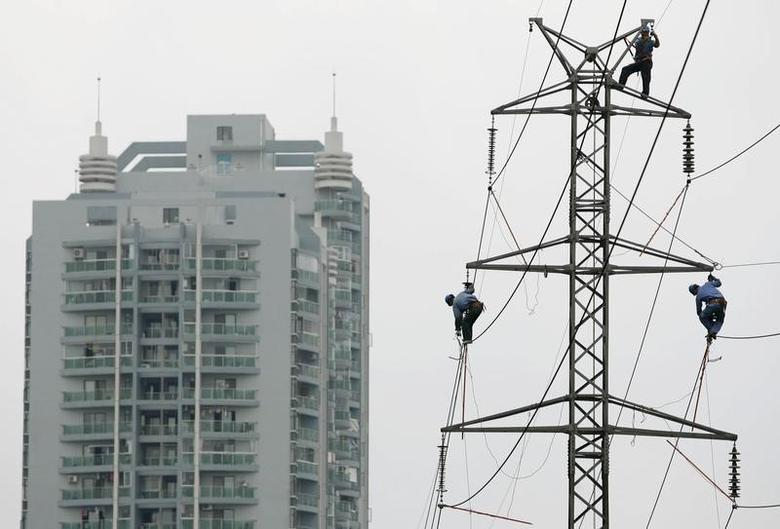 Labourers work on a power transmission tower near a residential building in Wuhan, Hubei province, June 30, 2008. REUTERS/Stringer