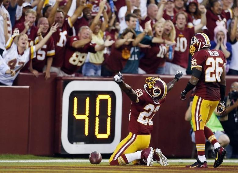 Washington Redskins' DeAngelo Hall celebrates a touchdown while on his knees during the first-half of their NFL football game against the Philadelphia Eagles in Landover, Maryland, September 9, 2013. REUTERS/Larry Downing