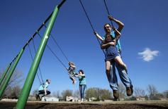 Joe Smith rides on a swing with his daughter Rowan as his wife Andrea plays with her children Norah and Chase  at a playground in Winthrop Harbor, Illinois, May 9, 2014. REUTERS/Jim Young