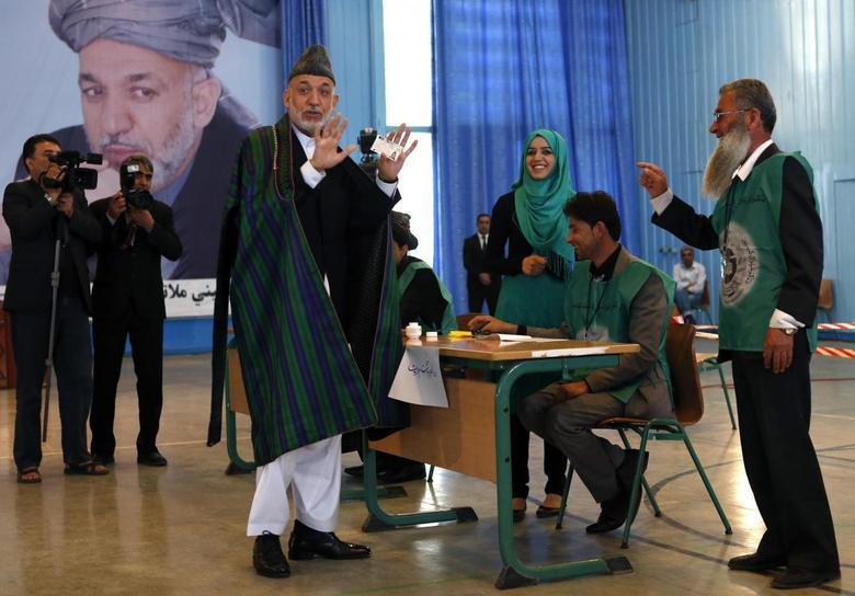 Afghan President Hamid Karzai shows his card before voting in the presidential election in Kabul June 14, 2014.  REUTERS/Mohammad Ismail