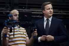 Britain's Prime Minister, David Cameron (R) visits Pinewood Studios in Buckinghamshire, January 11, 2012. REUTERS/Pool/Ben Stansal