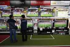 A shopper (L) looks at Sony Corp's Bravia television sets screening a soccer match at an electronics retail store in Tokyo June 10, 2014. REUTERS/Issei Kato