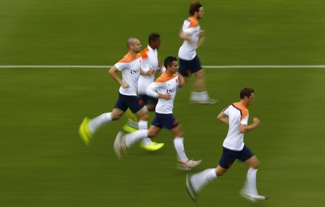 Netherlands' Robin Van Persie (C) and Ron Vlaar (L) run with teammates during a training session in Rio de Janeiro June 19, 2014.  REUTERS/Ricardo Moraes