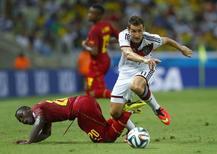 Miroslav Klose, da Alemanha, disputa a bola com jogadores de Gana durante jogo em Fortaleza. 21/06/2014. REUTERS/Eddie Keogh