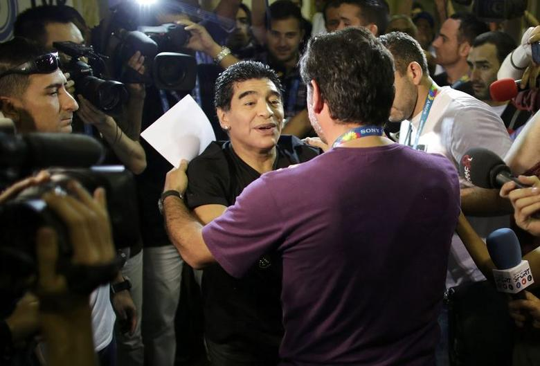 Former Argentine national soccer striker Diego Maradona greets a friend as he enters the studio of a public broadcast company at the International Broadcast Center of the 2014 World Cup in Rio de Janeiro, June 13, 2014.  REUTERS/Rickey Rogers