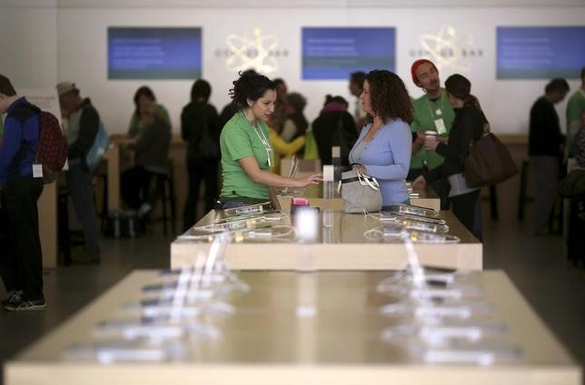 An Apple employee works with a customer in a retail store in the Marina neighborhood in San Francisco, California April 23, 2014. REUTERS/Robert Galbraith/Files