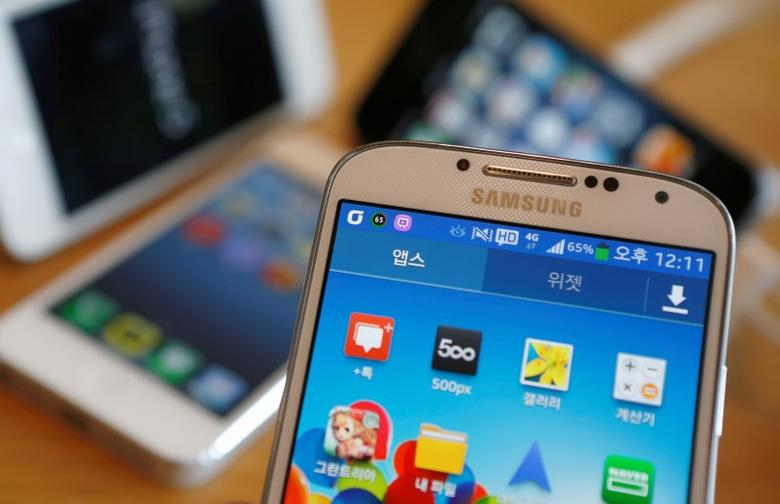 A Samsung Electronics' Galaxy S4 (front) and Apple's iPhone 5 smartphones are seen in this picture illustration taken in Seoul May 13, 2013. REUTERS/Kim Hong-Ji/Files