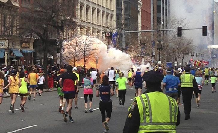 Runners continue to run towards the finish line of the Boston Marathon as an explosion erupts near the finish line of the race in this photo exclusively licensed to Reuters by photographer Dan Lampariello after he took the photo in Boston, Massachusetts, April 15, 2013. Mandatory Credit REUTERS/Dan Lampariello