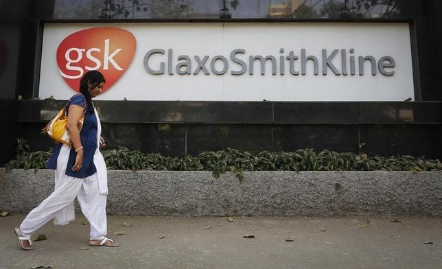 A woman walks past a GlaxoSmithKline Pharmaceuticals Ltd logo outside their headquarters in Mumbai December 16, 2013.  REUTERS/Danish Siddiqui