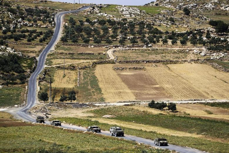 A convoy of Israeli military vehicles drives during an ongoing operation to locate three Israeli teens outside the West Bank City of Hebron June 17, 2014. REUTERS/Amir Cohen
