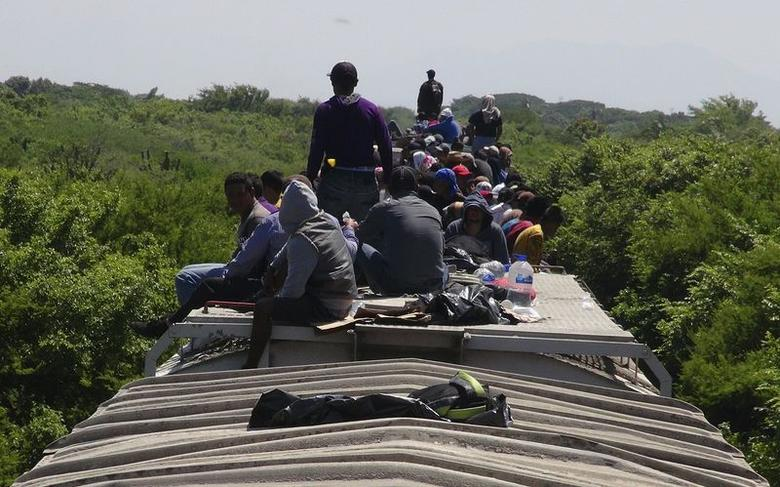 Unaccompanied minors ride atop the wagon of a freight train, known as La Bestia (The Beast) in Ixtepec, in the Mexican state of Oaxaca June 18, 2014.  REUTERS/Jose de Jesus Cortes