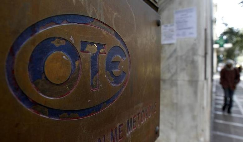 A man walks past a Hellenic Telecom (OTE) branch in central Athens June 6, 2011.     REUTERS/Yiorgos Karahalis