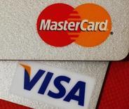 Карты MasterCard и VISA в Гонконге 8 декабря 2010 года. Российский Минфин сохранил для международных платежных систем Visa и MasterCard жесткие сроки, к которым они должны перевести внутрироссийские операции на локальные процессинги, но готов к их пересмотру при объективных причинах опоздания, сказал журналистам замминистра финансов Алексей Моисеев. REUTERS/Bobby Yip