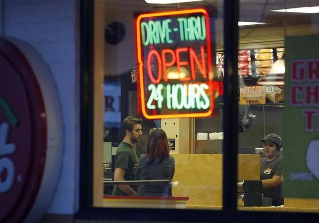 People stand at the counter at a Del Taco fast food restaurant which serves food 24 hours a day in Los Angeles, California, May 11, 2012. REUTERS/David McNew