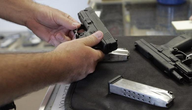 A customer inspects a 9mm handgun at Rink's Gun and Sport in the Chicago, suburb of Lockport, Illinois June 26, 2008.REUTERS/Frank Polich