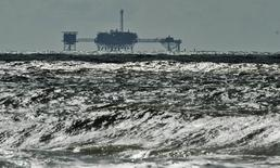 An oil and gas drilling platform stands offshore as waves churned from Tropical Storm Karen come ashore in Dauphin Island, Alabama, October 5, 2013.. REUTERS/Steve Nesius