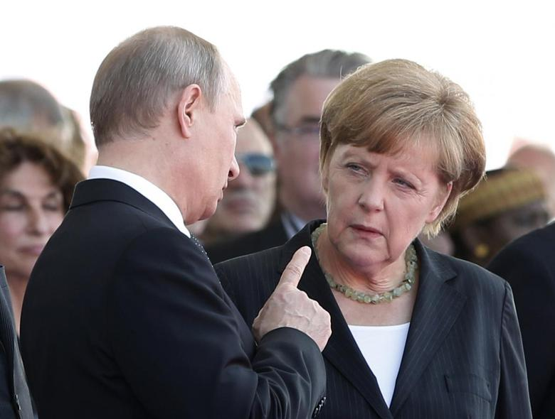 Russian President Vladimir Putin talks with German Chancellor Angela Merkel as they attend the International 70th D-Day Commemoration Ceremony in Ouistreham June 6, 2014. World leaders and veterans gathered by the beaches of Normandy on Friday to mark the 70th anniversary of the Allied D-Day landings that helped turn the tables in World War Two, with host France hoping the event will bring a thaw in the?Ukraine?crisis.  REUTERS/Kevin Lamarque  (FRANCE - Tags: POLITICS ANNIVERSARY CONFLICT TPX IMAGES OF THE DAY)