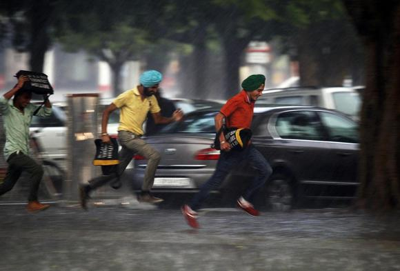 Men run for cover during a heavy rain shower in Chandigarh June 13, 2014. REUTERS/Ajay Verma/Files
