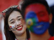 Болельщица Южной Кореи улыбается перед матче с Алжиром на чемпионате мира в Порту-Алегри 22 июня 2014 года.  Южная Корея в ночь на пятницу сыграет с командой Бельгии в матче группы H чемпионата мира в Бразилии. REUTERS/Murad Sezer