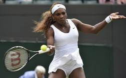 Serena Williams of the U.S. hits a return to Chanelle Scheepers of South Africa in their women's singles tennis match at the Wimbledon Tennis Championships, in London June 26, 2014.   REUTERS/Toby Melville