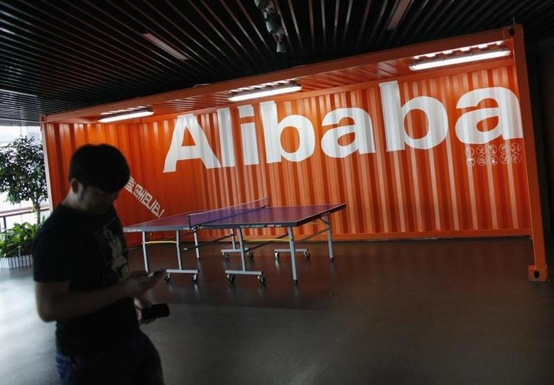 An employee walks past a logo of Alibaba (China) Technology Co. Ltd during a media tour organised by government officials at its headquarters on the outskirts of Hangzhou, Zhejiang province June 20, 2012. REUTERS/Carlos Barria/Files