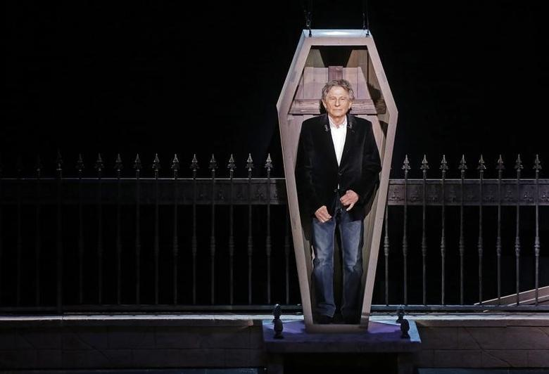 Polish-French film director Roman Polanski stands inside a coffin as he takes part in the presentation of the musical ''Le Bal des Vampires'' (Dance of the Vampires) at the Mogador theater in Paris March 17, 2014. REUTERS/Jacky Naegelen
