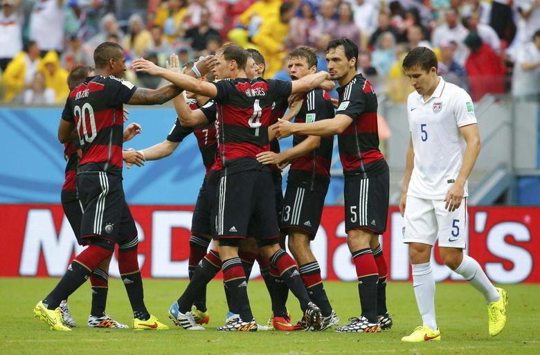 Germany's Thomas Mueller (3rd R) celebrates after scoring a goal with teammates as Matt Besler of the U.S. walks past during their 2014 World Cup Group G soccer match at the Pernambuco arena in Recife June 26, 2014. REUTERS/Laszlo Balogh