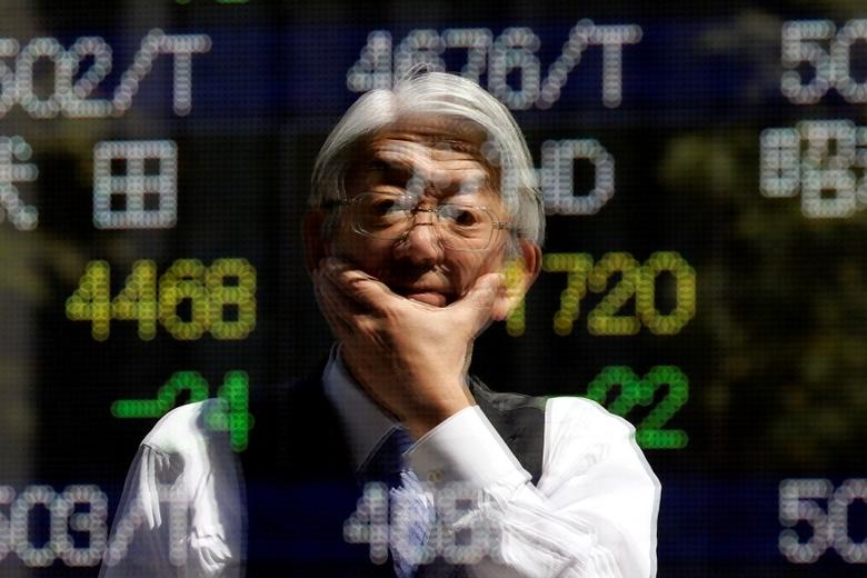 A man is reflected in an electronic stock quotation board outside a brokerage in Tokyo April 11, 2014. REUTERS/Issei Kato