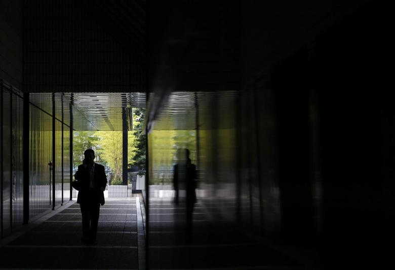 A man using a mobile phone walks down a corridor of a building at a business district in Tokyo June 26, 2014. REUTERS/Yuya Shino