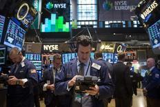 Трейдеры на торгах Нью-Йорской фондовой биржи 17 марта 2014 года. Уолл-стрит завершила торги четверга легким снижением после того, как президент Федерального резервного банка Сент-Луиса Джеймс Буллард высказался в поддержку повышения ставок чуть раньше планируемого ФРС срока. REUTERS/Brendan McDermid