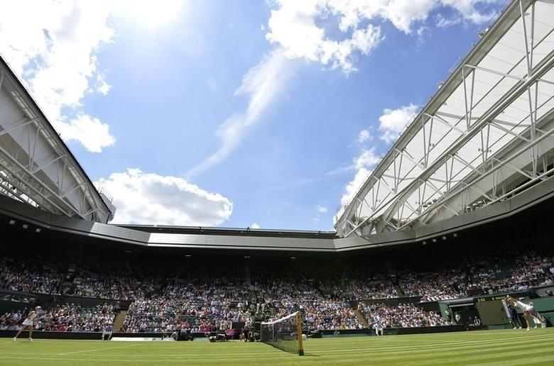 Casey Dellacqua of Australia (R) serves to Agnieszka Radwanska of Poland during their women's singles tennis match at the Wimbledon Tennis Championships, in London June 25, 2014.        REUTERS/Toby Melville