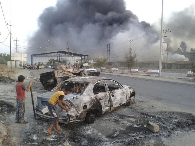 Civilian children stand next to a burnt vehicle during clashes between Iraqi security forces and al Qaeda-linked Islamic State in Iraq and the Levant (ISIL) in the northern Iraq city of Mosul, June 10, 2014. REUTERS/Stringer