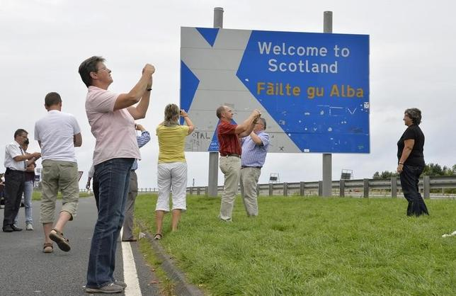 Swiss tourists take photographs next to a road that marks the England - Scotland border, at a lay-by on the A1 road near Berwick August 20, 2013.  REUTERS/Toby Melville