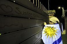 Torcedora do Uruguai escreve nome do jogador Luis Suárez em uma parede, à espera de sua chegada a Montevidéu. 26/6/2014 REUTERS/Carlos Pazos
