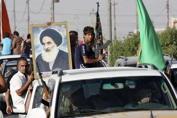 Volunteers, who have joined the Iraqi Army to fight against predominantly Sunni militants, carry weapons and a portrait of Grand Ayatollah Ali al-Sistani during a parade in the streets in Baghdad's Sadr city June 14, 2014. REUTERS/Wissm al-Okili/Files