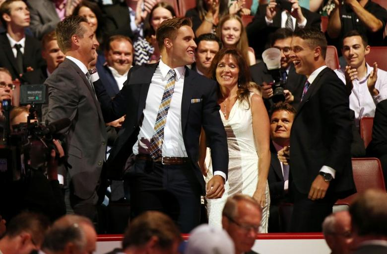 Aaron Ekblad (middle) reacts after being selected as the number one overall pick to the Florida Panthers in the first round of the 2014 NHL Draft at Wells Fargo Center. Mandatory Credit: Bill Streicher-USA TODAY Sports