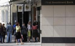 Las autoridades búlgaras dijeron el domingo que habían detenido a tres personas más por la sospecha de que habían participado en una trama para desestabilizar el sistema bancario del país al extender rumores falsos sobre la salud de sus bancos comerciales. En la imagen, gente hace cola fuera del una sucursal del banco búlgaro First Investment Bank, en Sofía el 27 de junio de 2014.  REUTERS/Stoyan Nenov