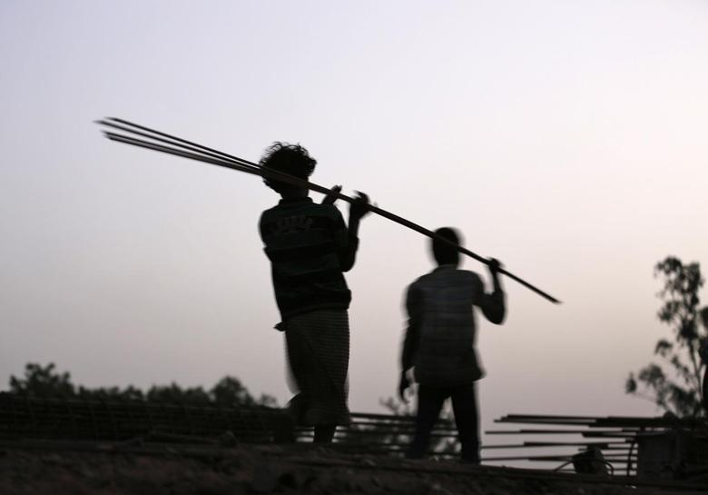 Labourers carry iron rods at the construction site of a flyover on the outskirts of the western Indian city of Ahmedabad June 24, 2014. REUTERS/Amit Dave