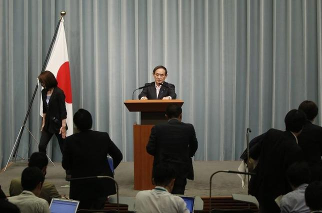 Japan's Chief Cabinet Secretary Yoshihide Suga (C) prepares to leave a news conference as reporters rush to leave from the conference room at Prime Minister Shinzo Abe's official residence in Tokyo May 29, 2014. REUTERS/Yuya Shino