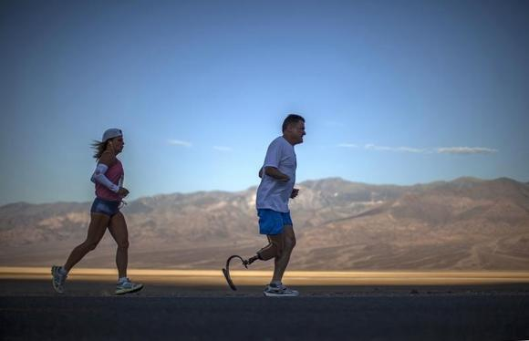 Chris Moon of Britain (R), 51, and Shannon Farar-Griefer, 52, of Hidden Hills, California, compete in the Badwater Ultramarathon in Death Valley National Park, California July 15, 2013. REUTERS/Lucy Nicholson