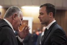 South African Olympic and Paralympic athlete Oscar Pistorius talks to his defence lawyer Barry Roux (L) during his murder trial in the North Gauteng High Court in Pretoria June 30, 2014. REUTERS/Ihsaan Haffejee/Pool