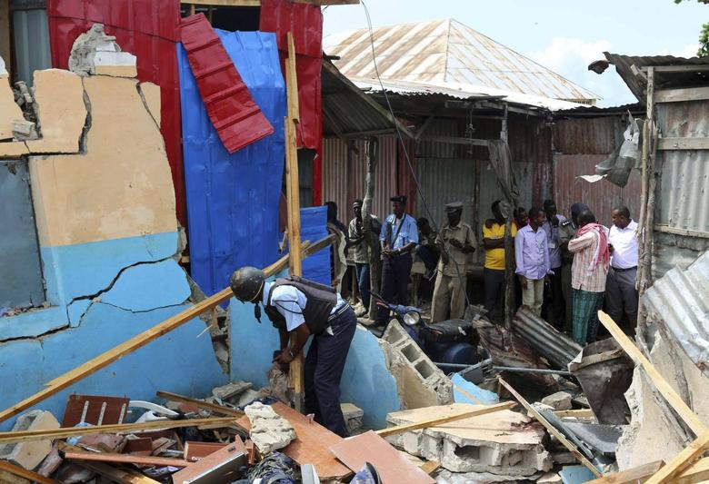 Somali policeman shifts through debris after a blast occurred at a government tax collection point near Kaaraan district, north of Mogadishu June 30, 2014. REUTERS/Feisal Omar