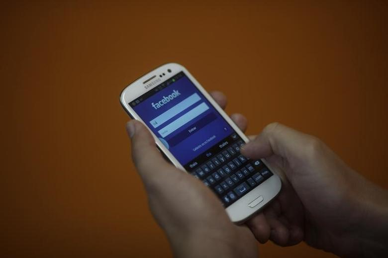 A smartphone user logs into his Facebook account in Rio de Janeiro April 15, 2013. REUTERS/Ricardo Moraes