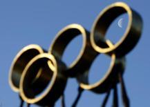 Луна на фоне олимпийских колец напротив штаб-квартиры МОК в Лозанне 9 декабре 2009. Украинский Львов отозвал заявку на зимние Олимпийские игры 2022 года и вместо этого бросит силы на борьбу за право проведения Игр в 2026 году, сообщил Международный олимпийский комитет (МОК) в понедельник. REUTERS/Denis Balibouse