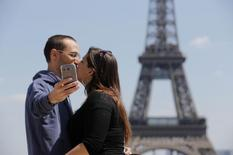 A couple of tourists use a mobile phone to take a selfie picture as they kiss at the Trocadero Square near the Eiffel Tower in Paris, May 16, 2014. REUTERS/Christian Hartmann