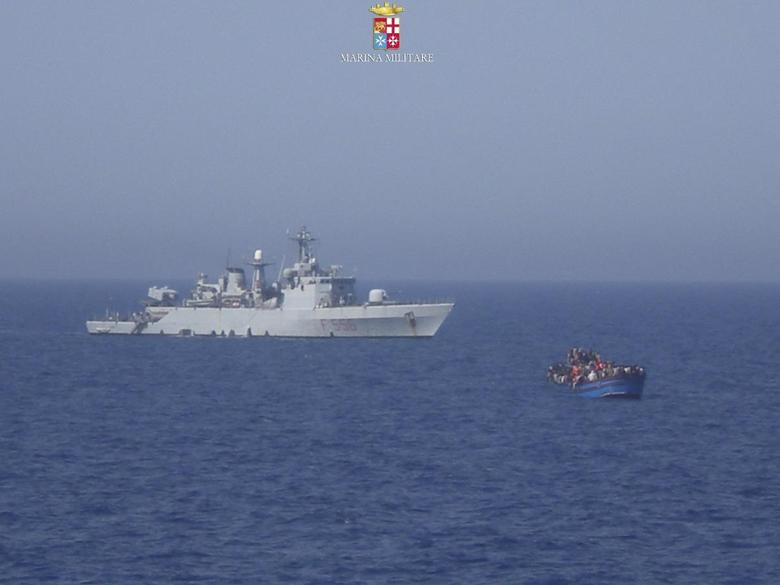 Migrants sit in their boat during a rescue operation by Italian navy ship Grecale (L) off the coast of Sicily, in this handout picture by the Italian Marina Militare June 29, 2014. REUTERS/Marina Militare/Handout via Reuters