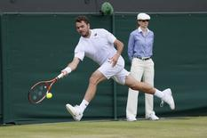 Stanislas Wawrinka of Switzerland hits a return to Denis Istomin of Uzbekistan during their men's singles tennis match at the Wimbledon Tennis Championships, in London June 30, 2014.          REUTERS/Stefan Wermuth