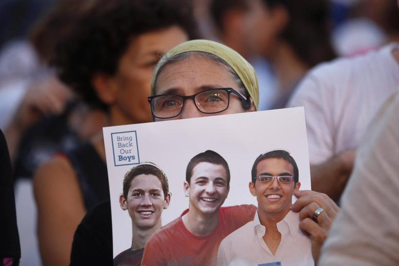 An Israeli woman holds a sign with images of three missing Israeli teenagers, at a rally in Rabin Square in the coastal city of Tel Aviv June 29, 2014. REUTERS/Baz Ratner